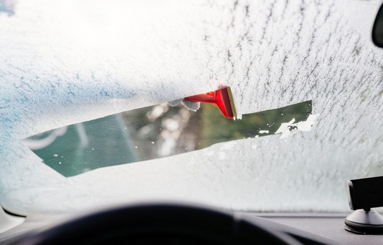 Woman deicing front car windshield with scraper. Car at winter. View from inside