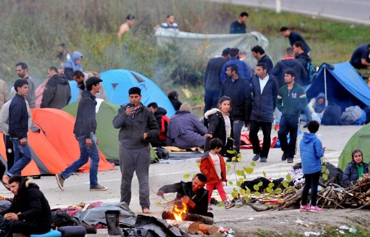 Asian migrants camp on the road in the vicinity of Maljevac border crossing with neighboring Croatia, near Northern-Bosnian town of Velika Kladusa, on October 24, 2018. - In their struggle with large number of in coming migrants, Bosnian authorities have provided two additional capacities, in abandoned army barracks in Hadzici and a former appliance factory in Bihac. Regardless of the authority's efforts, groups of migrants chose to leave Bosnia and attempt an illegal crossing into neighboring Croatia, hoping to travel further into the EU countries. (Photo by ELVIS BARUKCIC / AFP)        (Photo credit should read ELVIS BARUKCIC/AFP/Getty Images)